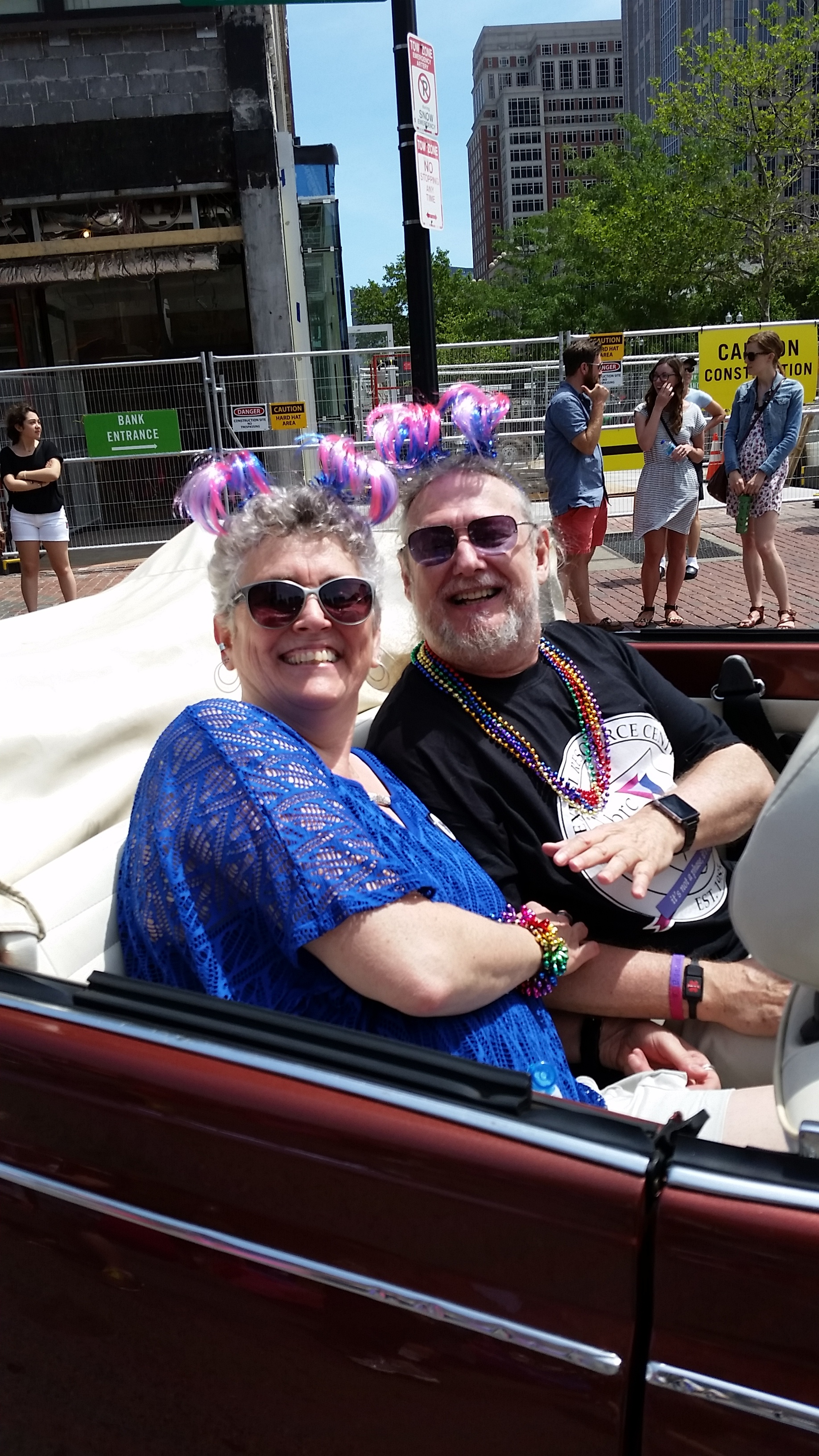 Ellyn and Woody, wearing bi-colored ribbon headbands, pose in a car at Pride 2015