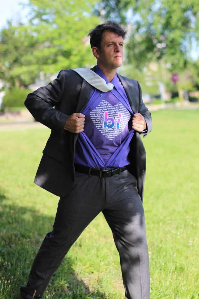 Man in suit opens shirt to reveal a bi word cloud shirt, superman-style