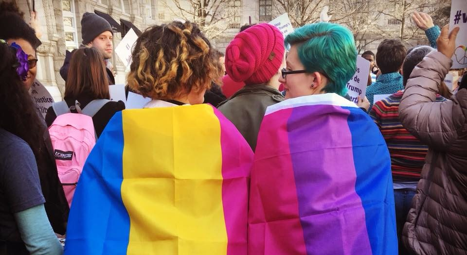 Two people of about the same height, one with short curly brown hair and one with short green hair, wrapped in flags: a pink, yellow, and blue pansexual flag, and a pink, purple, and blue bi+ flag.