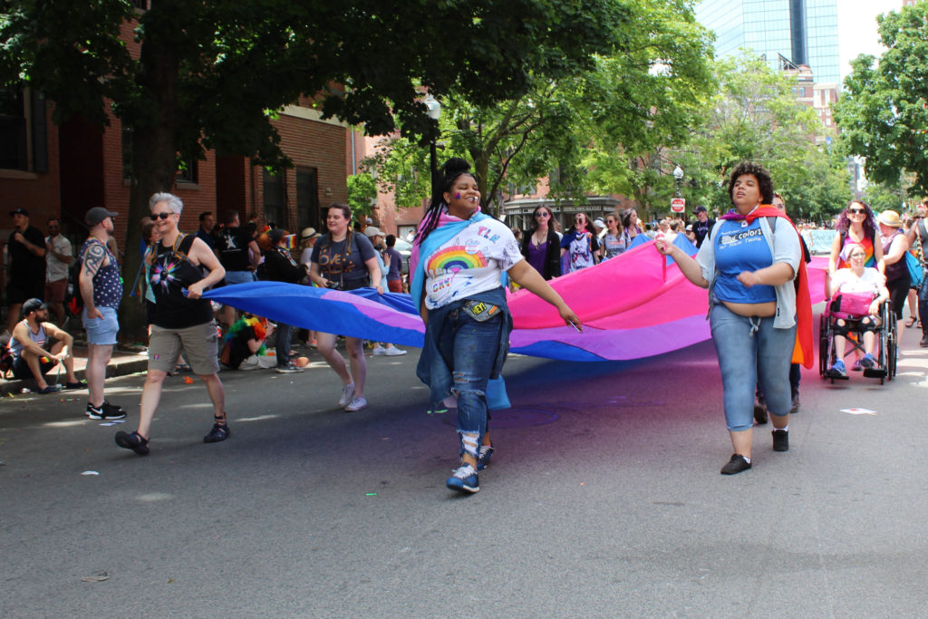 People carrying a 40-foot bi pride flag down a city street