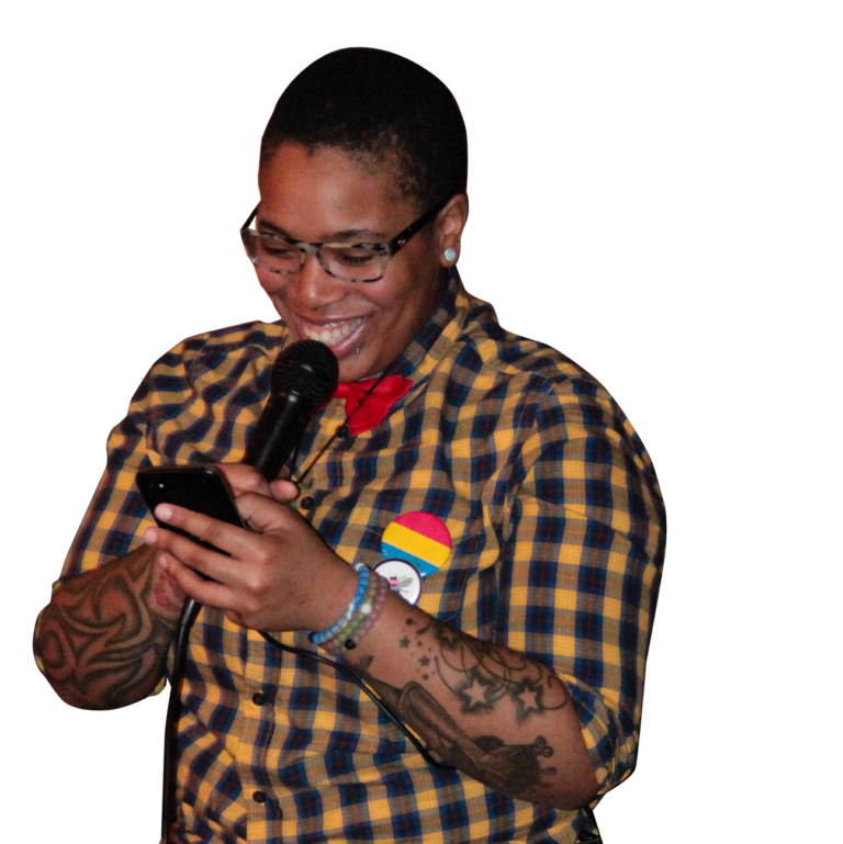 Person speaking into microphone while looking at phone and wearing bee and pansexual flag pins
