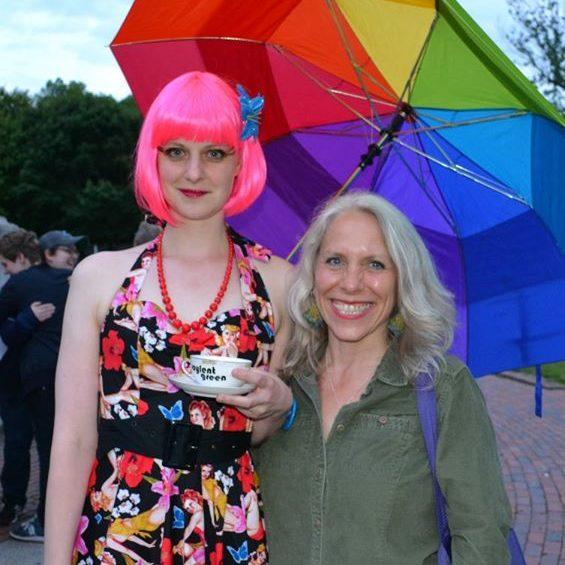 Tiggy Upland and Robyn Ochs posing for the camera beneath a rainbow umbrella