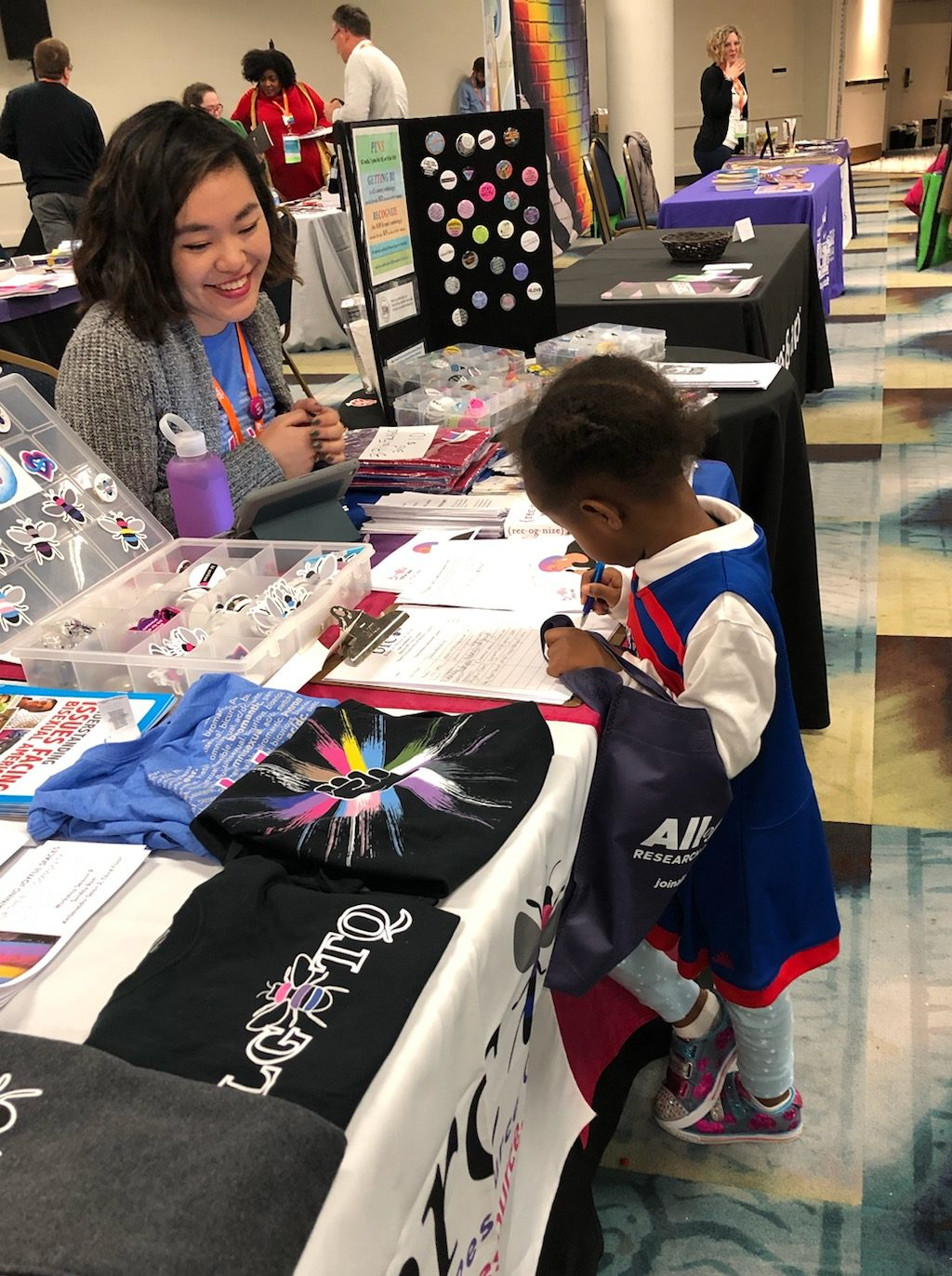 BRC board member behind merchandise table smiles at a young child who draws on the sign-up sheet